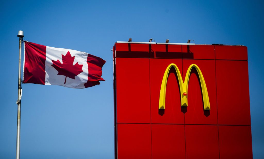 A Canadian flag waves beside McDonalds fast food restaurant in Toronto